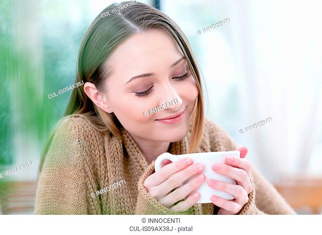 Woman holding coffee cup eyes closed smiling