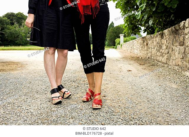 Women wearing sandals on gravel path