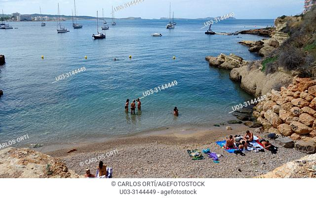 Tourists bathing in a small beach close to the balearic town of Sant Antoni de Portmany, island of Ibiza, Spain, Europe