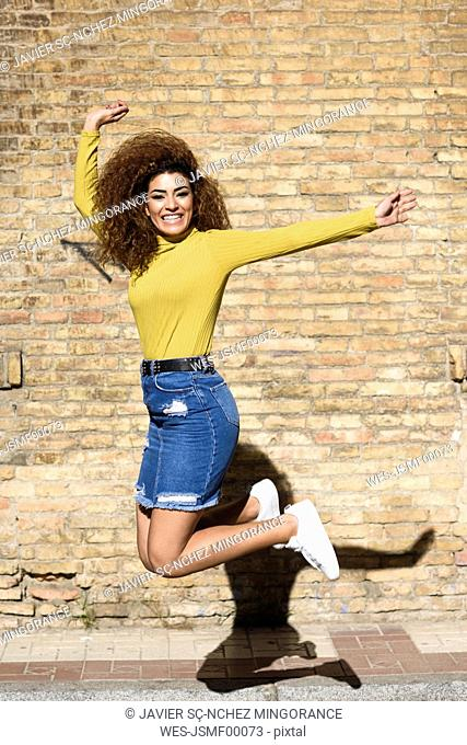 Happy young woman jumping in the air