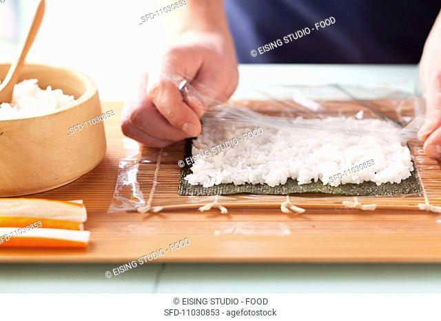 Preparing California rolls: lay cling film over the rice