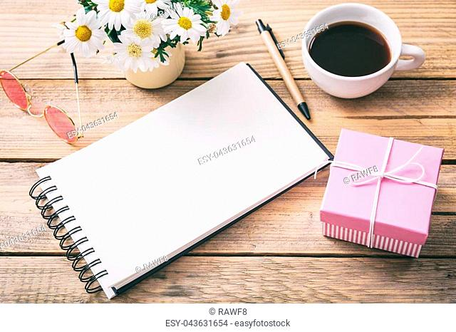 Gift for a woman. Pink gift box and a blank empty notebook, office desk background, view from above, space for text