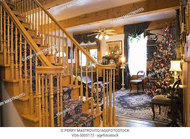 Wooden staircase and living room with Christmas tree inside an old 1904 Victorian cottage style residential home, Quebec, Canada