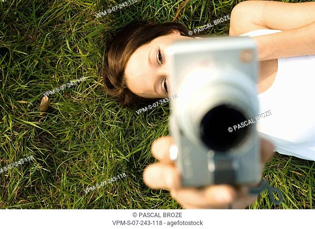 High angle view of a young woman lying on grass and holding a digital camera