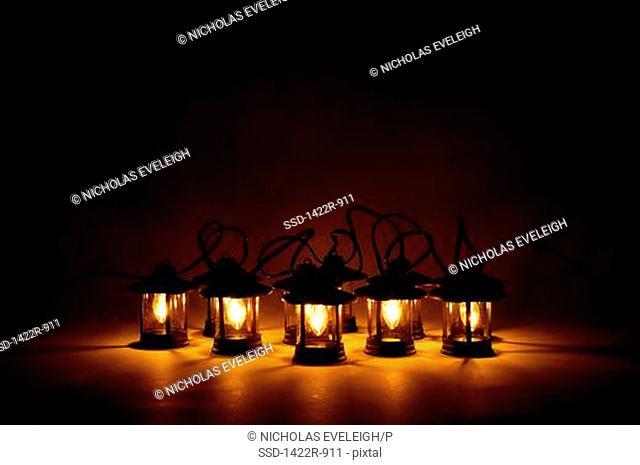 Electric lanterns glowing warm light in darkness