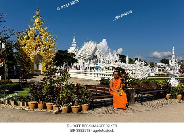 Monk sitting in front of the ornate golden entrance of Wat Rong Khun, White Temple, by architect Chalermchai Kositpipat, Chiang Rai, Chiang Rai Province