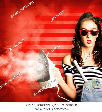 Quirky retro photo of a sexy pinup girl in retro style completing domestic chores with red hot iron. Pin up housekeeping maid