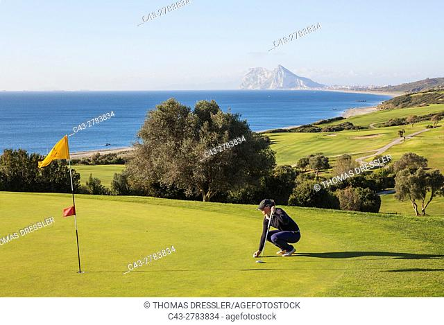 Golfer at a green at the La Alcaidesa Golf Resort. In the background the Mediterranean Sea with the Rock of Gibraltar (British)
