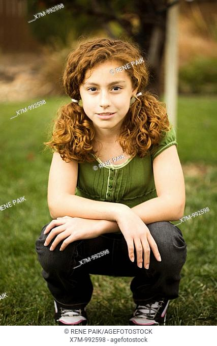 Smiling red-headed young mixed race mexican & caucasian girl in pigtails