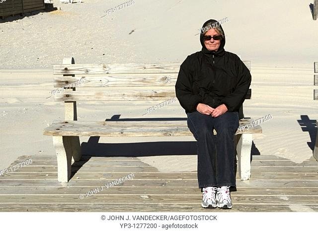 A middle-aged woman sitting on a wooden bench at the end of a seaside boardwalk smiling  Fall/Winter  Lavalette, New Jersey, USA