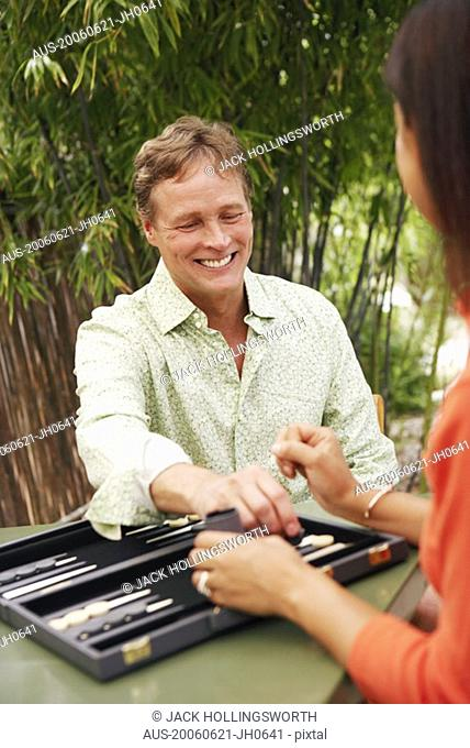 Close-up of a mature man playing backgammon with a mature woman