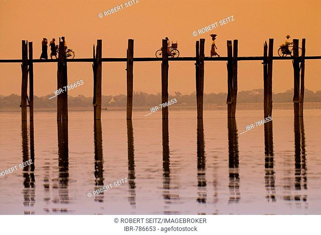 Cyclists and pedestrians crossing the U Bein Bridge at sunset, old wooden teak bridge, Mandalay, Myanmar, Southeast Asia