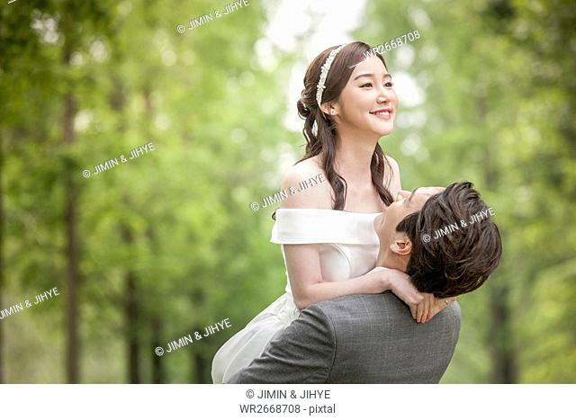 Portrait of young smiling wedding couple holding outdoors
