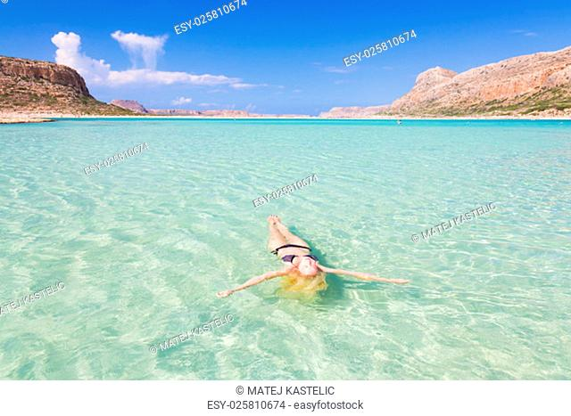 Beautiful Caucasian woman floating in turquoise blue lagoon