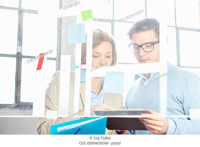 Businessman and woman looking at digital tablet