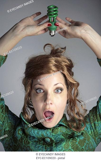 Portrait of a worried woman holding energy efficient lightbulb over her head