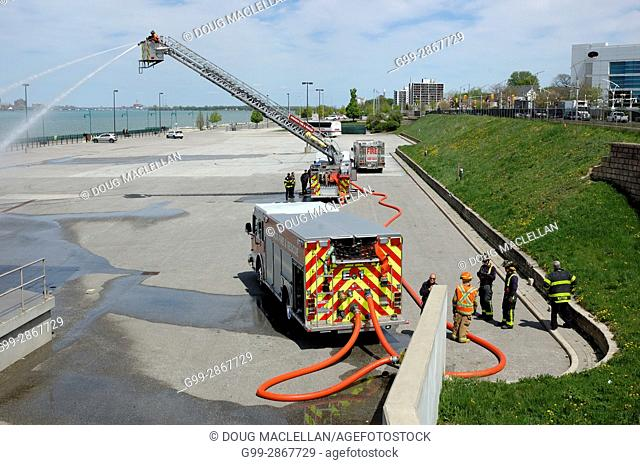 A fireman in a bucket aims a hose on a cement area of a public plaza while other fireman watch during a maintenance procedure at the Festival Plaza in Windsor