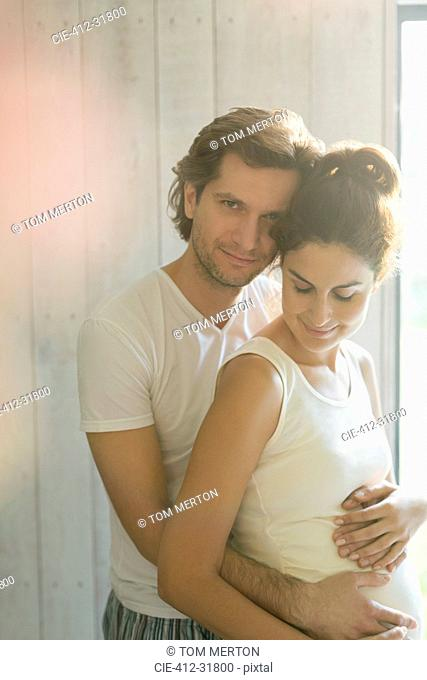 Portrait affectionate pregnant couple hugging