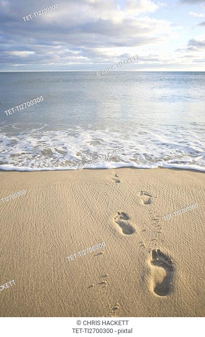 USA, Massachusetts, Cape Cod, footprints on beach at sunset