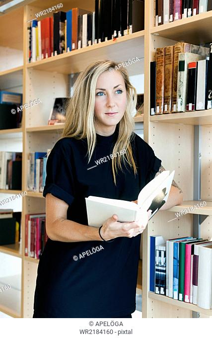 Thoughtful female student looking away while holding book in college library