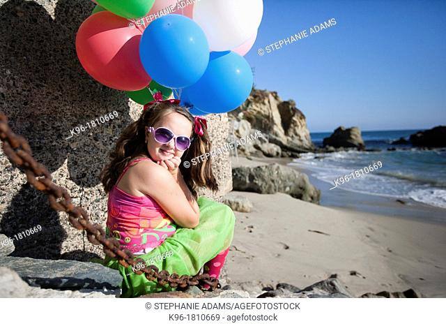 little girl sitting at the ocean with balloons, looking at the camera