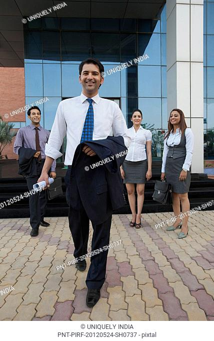 Happy businessman walking with their colleagues in the background
