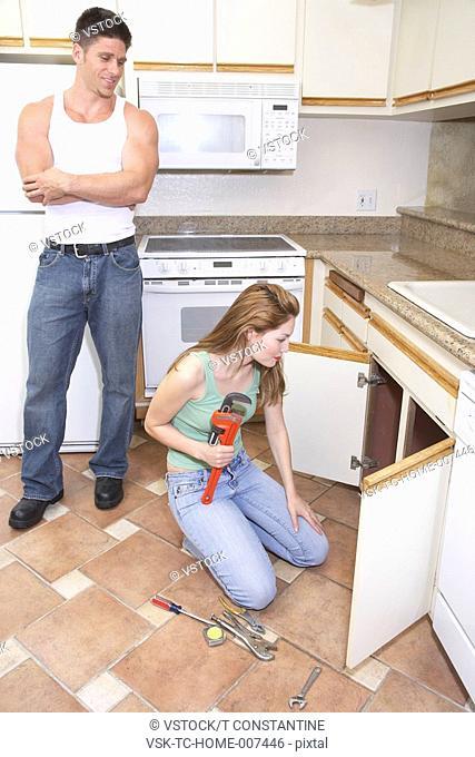 Man watching female plumber fixing kitchen sink