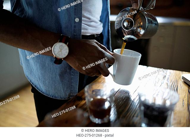 Entrepreneurial coffee roaster pouring coffee into mug