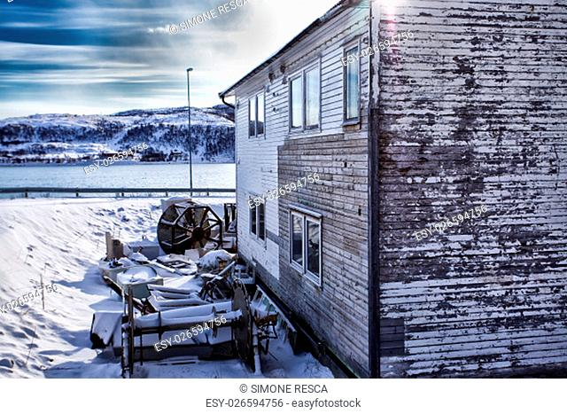 Weathered house covered by snow in front of the norwegian sea