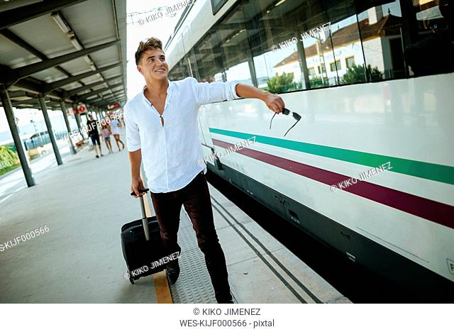 Young man at station platform running to get on the train