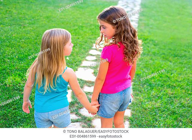 friends sister girls together in grass garden track holding hand looking eachother