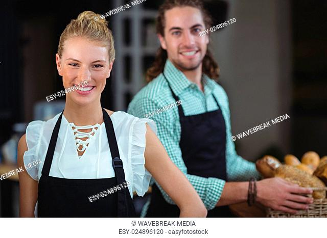 Portrait of waiter and waitress working behind the counter