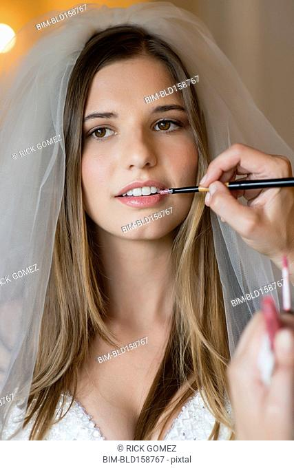 Caucasian stylist applying makeup on bride