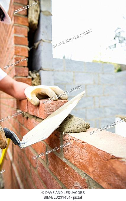 Caucasian construction worker laying bricks with mortar