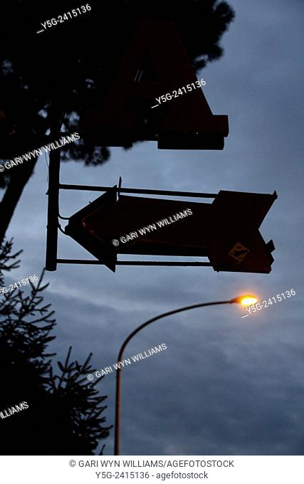 Arrow sign and street light at night in Rome Italy