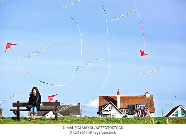 Woman on bench and kites flying