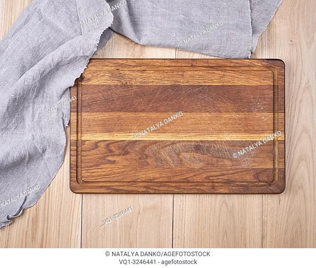 Empty old wooden kitchen cutting board and a gray towel on a table, the view from the top