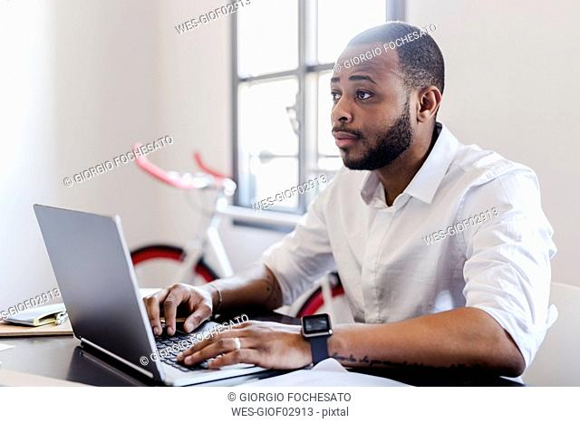 Man using laptop at desk in home office