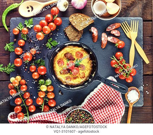 black round frying pan with fried omelette, next to fresh ripe red cherry tomatoes, close up