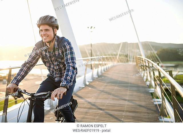 Young man riding bicycle on a bridge at sunset