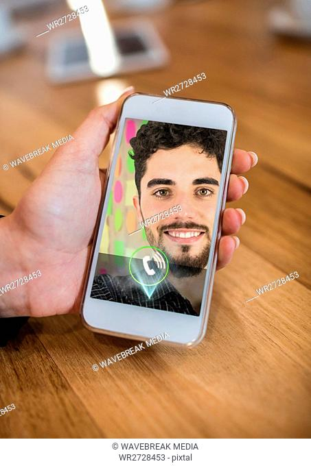 Hand holding mobile phone displaying man on video call screen