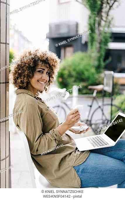 Woman working in a cafe, drinking coffee, using laptop
