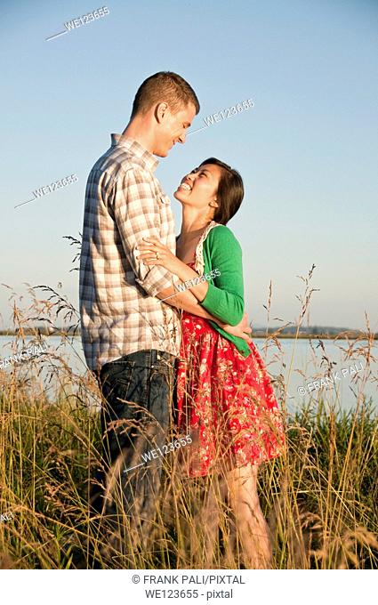 Standing in tall grass is a mixed race couple arm in arm