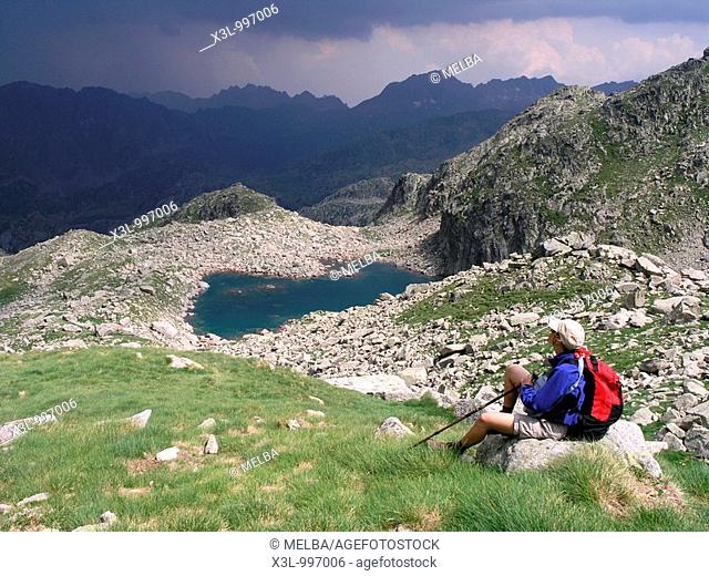 Mountain hiker resting in Port del Caldes lake while storm is coming  Aiguestortes National Park  Pyrenees  Lerida  Catalonia  Spain