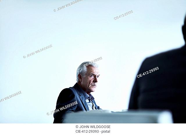 Serious senior businessman listening in meeting