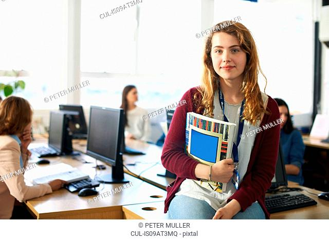 Portrait of female student holding file infront of computer class
