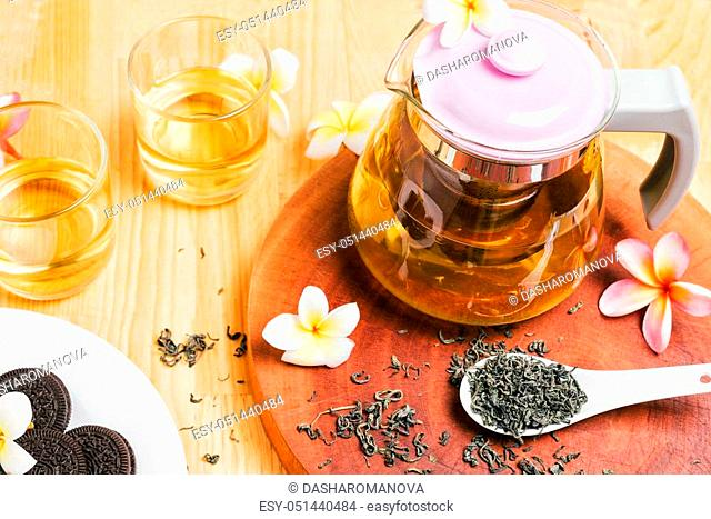 Cup of Chinese tea with teapot on wooden table with cookies. Frangipani flowers, spoon