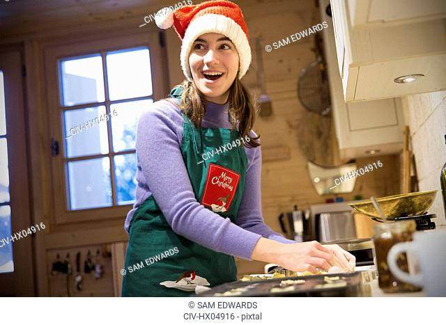 Smiling teenage girl in Christmas apron and Santa hat baking in kitchen