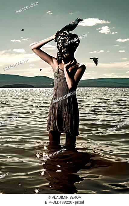 Caucasian woman wearing mask in lake