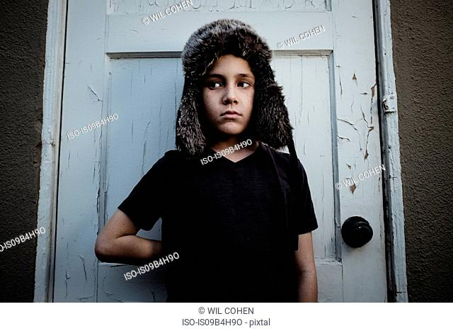 Boy wearing trappers hat standing against door